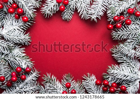 Merry Christmas and Happy Holidays greeting card, frame, banner. New Year. Noel. Silver, white and red Christmas ornaments and fir tree on red background top view. Winter holiday xmas theme. #1243178665
