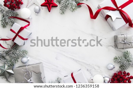 Merry Christmas and Happy Holidays greeting card, frame, banner. New Year. Red, silver Christmas gifts, presents and ornaments on white marble background top view. Winter holiday xmas theme. Noel. Fla #1236359158