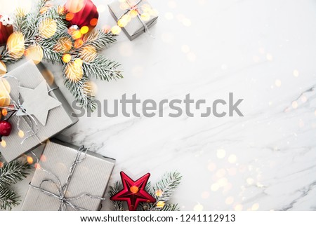 Merry Christmas and Happy Holidays greeting card, frame. New Year. Red, silver Christmas gifts, presents and ornaments on white marble background top view. Winter holiday xmas theme. Noel. Flat lay. #1241112913