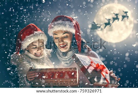 Merry Christmas and Happy Holidays! Mom and daughter are opening gift outdoors. Xmas night. Santa Claus flying in his sleigh against moon sky. Portrait loving family close up.