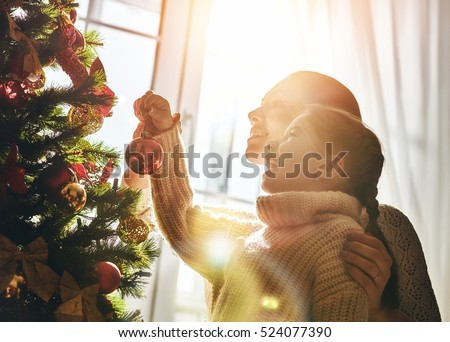 Merry Christmas and Happy Holidays! Mom and daughter decorate the Christmas tree indoors. The morning before Xmas. Portrait loving family close up. #524077390