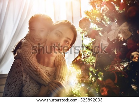 Merry Christmas and Happy Holidays! Mom and daughter decorate the Christmas tree indoors. The morning before Xmas. Portrait loving family close up. #525892033