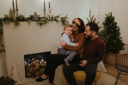Merry Christmas and Happy Holidays! Pretty family spend good time together in front of the fireplace.