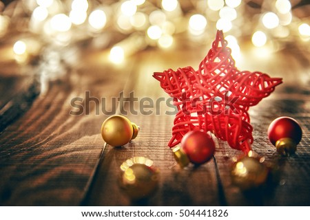 Merry Christmas and Happy Holidays! Red star, Christmas baubles and garland lights on old dark wooden rustic background.