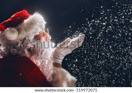 Shutterstock Merry Christmas and happy holidays! Santa Claus blows snow.