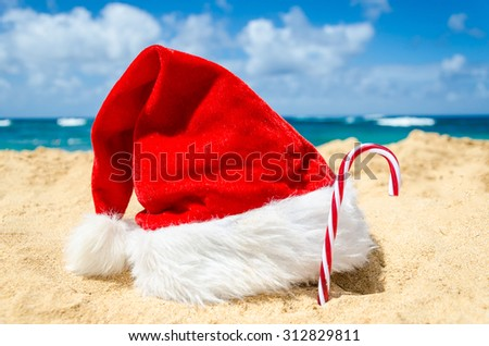 Merry Christmas and Happy New Year background with Santa Claus Hat and candy on the tropical beach near ocean in Hawaii #312829811