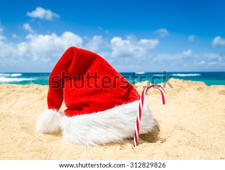 Merry Christmas and Happy New Year background with Santa Claus Hat and candy on the tropical beach near ocean in Hawaii #312829826