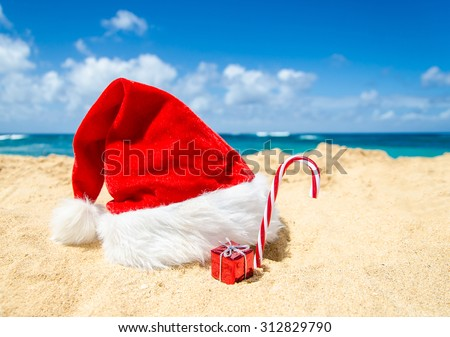 Merry Christmas and Happy New Year background with Santa Claus Hat, candy and gift on the tropical beach near ocean in Hawaii #312829790