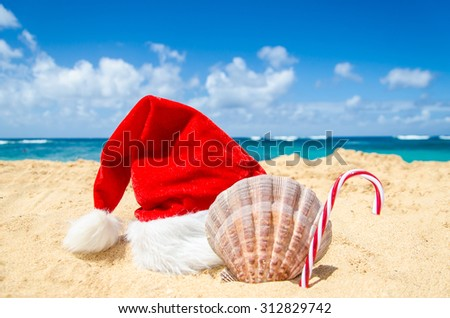 Merry Christmas and Happy New Year background with Santa Claus Hat, candy and seashell on the tropical beach near ocean in Hawaii #312829742