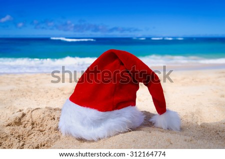 Merry Christmas and Happy New Year background with Santa Claus Hat on the tropical beach near ocean in Hawaii #312164774