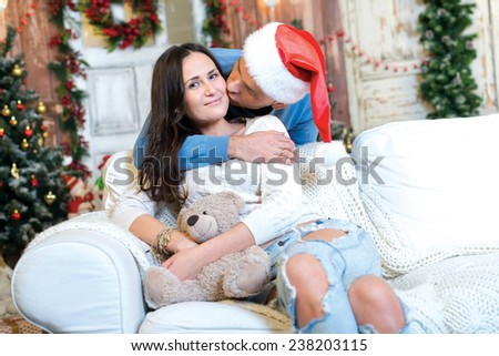 Merry Christmas and Happy New Year. Couple in love is sitting in festive Christmas decorated living room. Man is kissing his girlfriend, while she is happy just before New Year