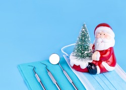 Merry Christmas And Happy New Year From Dentist Set of Dental Tools And Santa Claus On Blue Background.