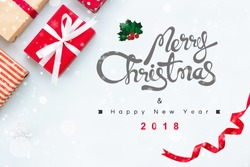 Merry Christmas and Happy New Year 2018 greeting text with gift boxes, white snow and curled red ribbon at border, top view