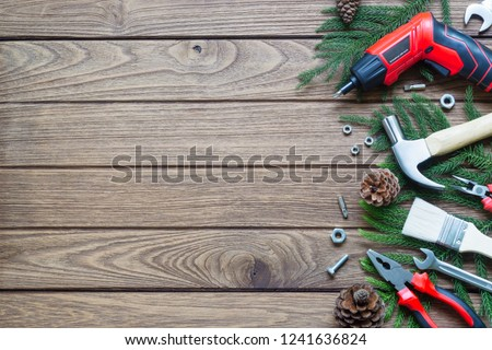 Merry Christmas and Happy new year handy construction tools background concept. Hammer, wrenches, screwdriver, pliers, paint brush, pine leaves, pine cones decoration on wood background. Top view with