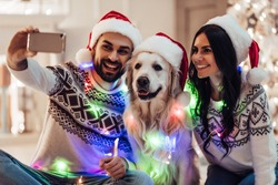 Merry Christmas and Happy New Year! Happy couple with dog labrador retriever waiting for the New Year in Santa Claus hats while sitting near beautiful Christmas tree at home. Smiling and making selfie