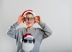 Merry christmas and happy new year. Happy smiling kid in a red hat and glasses. School child opens his eyes in surprise. Stylish boy in modern sweater with Santa Clause face. Funny kid portrait.