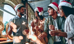 Merry Christmas and Happy New Year 2020!Multiracial young creative people are celebrating holiday in modern office. Group of young business people are drinking champagne with sparkling bengal light.