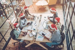 Merry Christmas and Happy New Year 2018!Multiracial young creative people are celebrating holiday in modern office. Group of young business people are sitting in Santa hats in last working day.