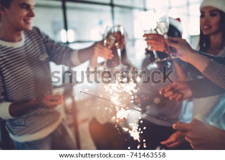 Merry Christmas and Happy New Year 2018!Multiracial young creative people are celebrating holiday in modern office.Group of business people drinking champagne with sparkling bengal lights in coworking
