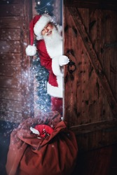 Merry Christmas and happy New Year! Santa Claus comes in a wooden house from the cold with a bag of presents and smiles.
