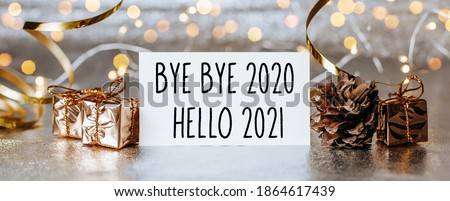 Photo of  Merry christmas and merry new year concept with gift boxes and greeting card with text Bye bye 2020 Hello 2021