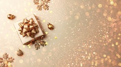 Merry Christmas card made of gift box, golden decoration, sparkles and confetti on gold background. Xmas and New Year holiday, bokeh, light. Flat lay, top view