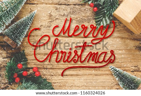 Merry Christmas card on wood floor top view handwriting red xmas on wooden table with mini christmas tree and mistletoe and home toy decoration with snow fall.happy winter holiday festive seasonal #1160324026