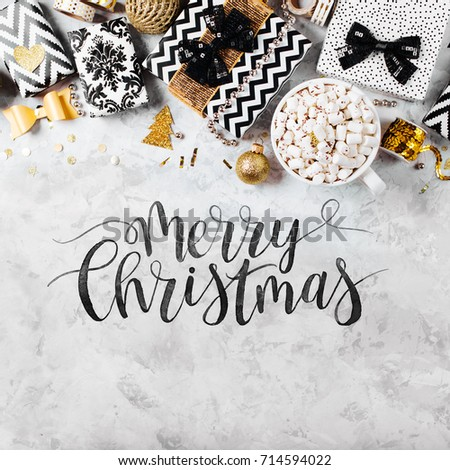 Merry Christmas Card with black and gold Christmas gifts, bows and decorations. Flat lay, top view.