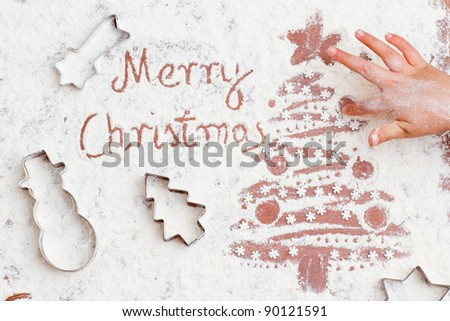 Merry Christmas -  child is painting the Christmas tree with fingers of the flour