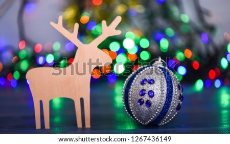 Merry Christmas concept. Ball with ornaments and wooden deer toy on blurred colorful garland background. Christmas decor. Symbols of winter holiday christmas. Deer and toy decorative ornament. #1267436149