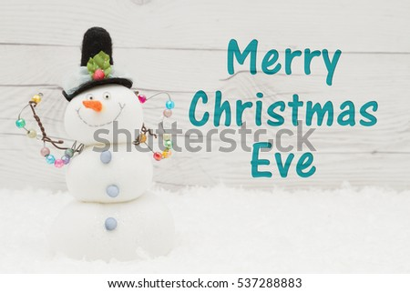 Merry Christmas Eve greeting, Some snow and a snowman on weathered wood with text Merry Christmas Eve #537288883
