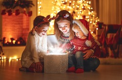 Merry Christmas! family mother and children with magic gift at home near  Christmas tree and fireplace