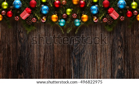 Merry Christmas Frame with real wood green pine, colorful baubles, gift boxe and other seasonal stuff over an old wooden aged background #496822975