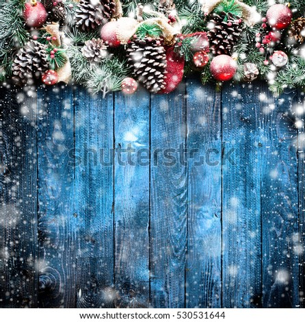 Merry Christmas Frame with Snow and real wood green pine, colorful baubles, knots with berries and other seasonal stuff over an old wooden aged background #530531644