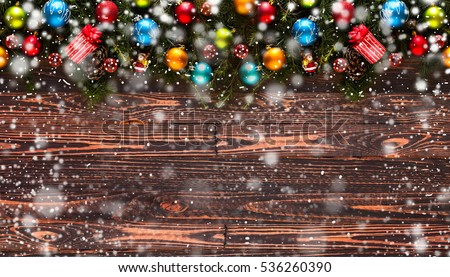 Merry Christmas Frame with Snow and real wood green pine, colorful baubles, knots with berries and other seasonal stuff over an old wooden aged background #536260390