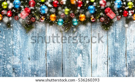 Merry Christmas Frame with Snow and real wood green pine, colorful baubles, knots with berries and other seasonal stuff over an old wooden aged background #536260393