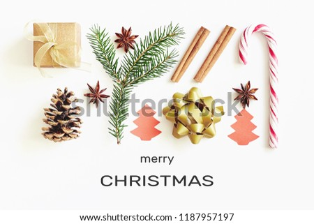 Merry Christmas greeting card. Gift box, ribbon, fir branches, cones, star anise, cinnamon, candy cane and paper christmas tree on white background with congratulation text.   #1187957197