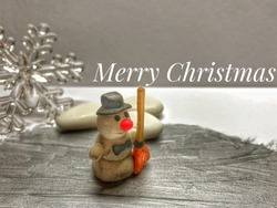 Merry Christmas greeting Card. Snowman on silver background, snowflake and white Candy in background. Holliday concept.