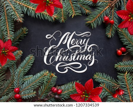 Merry Christmas hand lettering inscription with golden balls, tree branches and cones on a wooden background. Christmas greeting card.  #1207334539