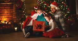 Merry Christmas! happy family mother father and children with magic gift near tree at evening at home