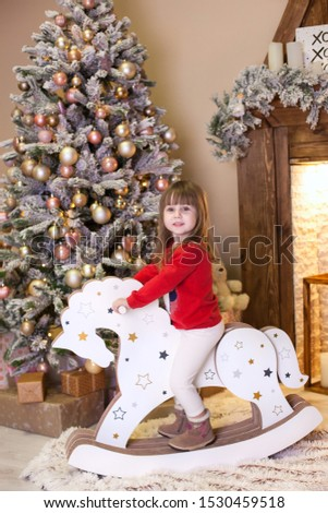Merry Christmas, happy holidays! New Year. little girl in red pajamas rides a wooden horse at home. child riding a cardboard horse near Christmas tree in living room. Holiday concept. Holiday concept #1530459518
