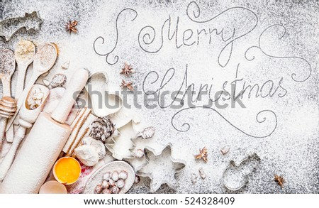Merry Christmas Inscription on Amazing Christmas Background with Flour, Eggs, Spices, Rolling Pin, Spoons and other Christmas ingredients and Utilities, Top View