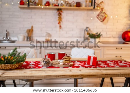 Merry Christmas! Interior decorated kitchen with Christmas decor and Christmas tree. table with hot drinks in fancy mugs with cookies and gingerbread. Christmas in kitchen table setting.