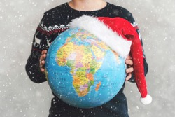 Merry Christmas. kid holding earth globe with a Santa hat with snowflakes