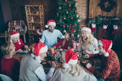 Merry christmas large family reunion gathering meeting sit table have x-mas feast father in santa claus hat cap joke mature people speak small little kids laugh wear reindeer headband in house