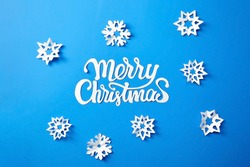 Merry Christmas lettering. Text with white snowflakes on blue paper background. Christmas holidays greeting card design.
