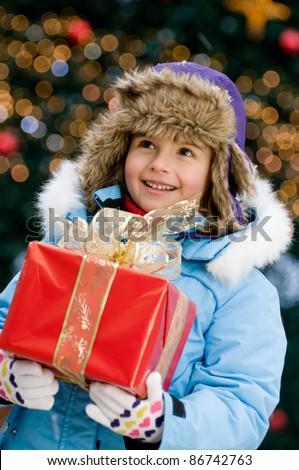Merry Christmas - Little girl with Christmas gift - Defocused Christmas Tree Lights