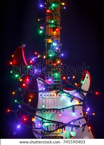 Shutterstock Merry christmas music guitar wrapped by colorful garland as a gift background