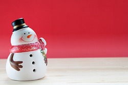 Merry Christmas or Happy New Year background concept : Cute snowman on  wood, red background