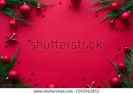 Merry Christmas red background decorated with happy 2021 new year tree branches and baubles stars, winter holiday card decorations festive merry concept, flat lay, above top view, copy space